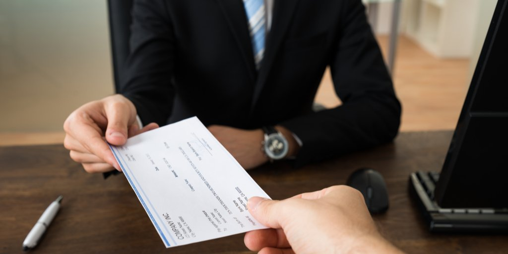 employer handing candiate salary pay check